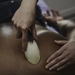 Photo of Margarita administering Gua Sha treatment