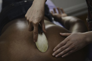 Photo of Margarita administering Gua Sha treatment