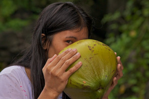 A woman enjoying a drink of green coconut. Photo under creative commons by David Spencer.